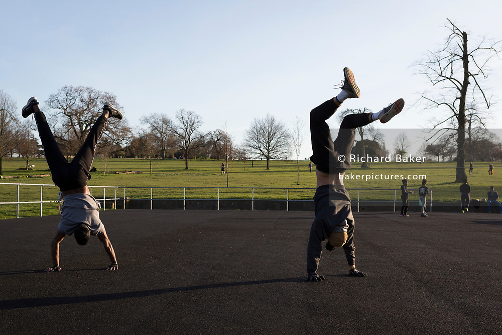 The day after UK Prime Minister Boris Johnson imposed unprecedented restrictions of movement for millions of Britons who were told to stay at home unless their key jobs or journeys were essential. Told to take a single exercise session per day, two young men practice their handstands at a clear space for those wishing to work out on a soft surface, where south Londoners use their local green space for a daily activity in Brockwell Park in Herne Hill SE24, on 24th March 2020.