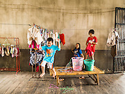 17 MARCH 2015 - BANGKOK, THAILAND: Children of firefighters hang their laundry in a lobby in the old Customs House in Bangkok. The old Customs House was once the financial gateway to Thailand (before 1932 called Siam). It was designed by an Italian architect in the 1880s. In the 1950s, customs moved to new, more modern building and the Customs House became the headquarters for the Marine firefighters. The firefighters now live in the decrepit buildings with their families.    PHOTO BY JACK KURTZ