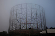 Thick fog obscures a gas tower in  London making a peaceful yet eerie landscape atmosphere as structures appear and disappear over the River Thames. Modern and old industrial and commercial architecture is releaved through a mist which lasted tthrough the entire day.