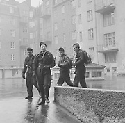 Four male chimney sweeps outside an apartment block on rainy day, Helsinki, Finland 1958