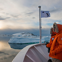 Guests on the bow of the National Geographic Explorer observe the stunning landscape after the ship exited the Lemaire Channel in Antarctica.