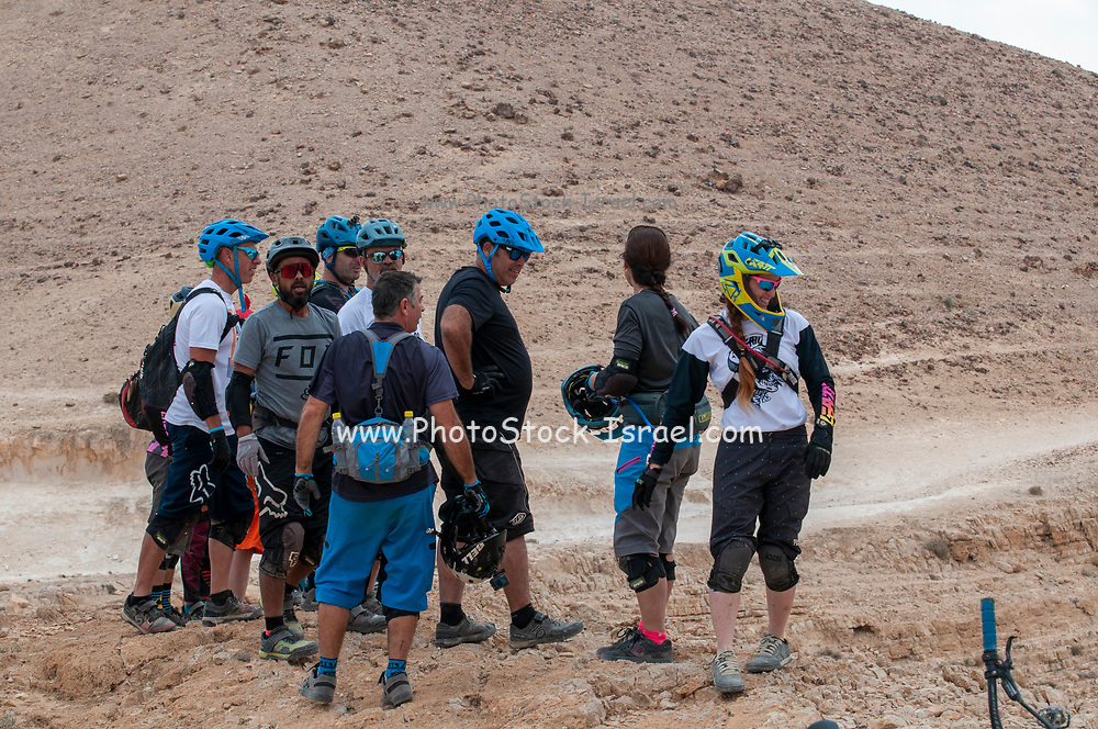 A group of cyclistin the Negev desert resting with green helmets