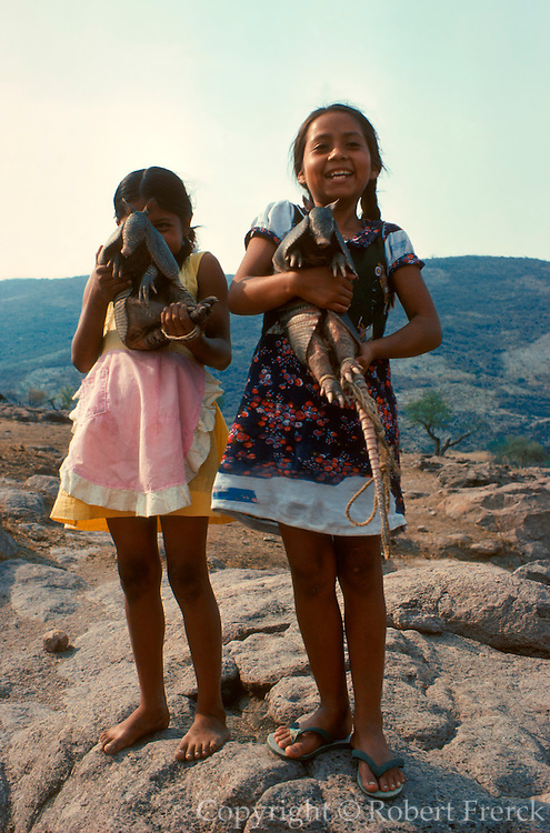 MEXICO, PEOPLE, VILLAGES Girls selling armadillos near Taxco
