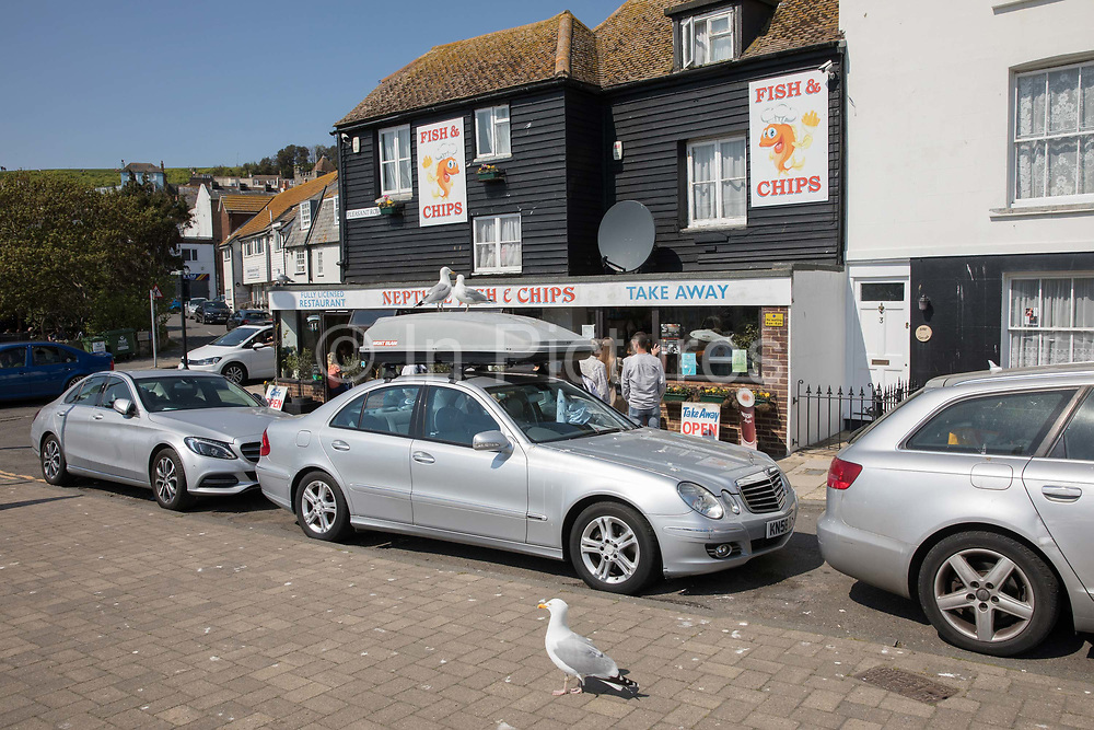 Seagulls gather outside a fish and chip take away shop on the 20th April 2019 in Hastings in the United Kingdom. Hastings is a town on England's southeast coast, its known for the 1066 Battle of Hastings.