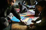 Noor Agha's family; (from left) Noor Agha himself, Yassin, 9, Noyi, 18, his first wife, Marzia, 46, Sobra, 7, and Saber, 8, make kites inside the house, Kabul, Afghanistan, Tuesday, March, 13, 2007. Noor Agha is a renowned kite maker who made kites for the movie makers of the best-selling novel, The Kite Runner, which will be distributed by Dreamworks and Paramount Vantage in Nov. this year. Noor Agha's wives, using their special glue, help him produce enough kites to please the clients' needs. Some of his children can also make their own kites with plastic bags and bamboo sticks. As the Afghan New Year's Day (Nawruz) approaching on March 21, the finger tips of Noor Agha's family got busier for mass production.