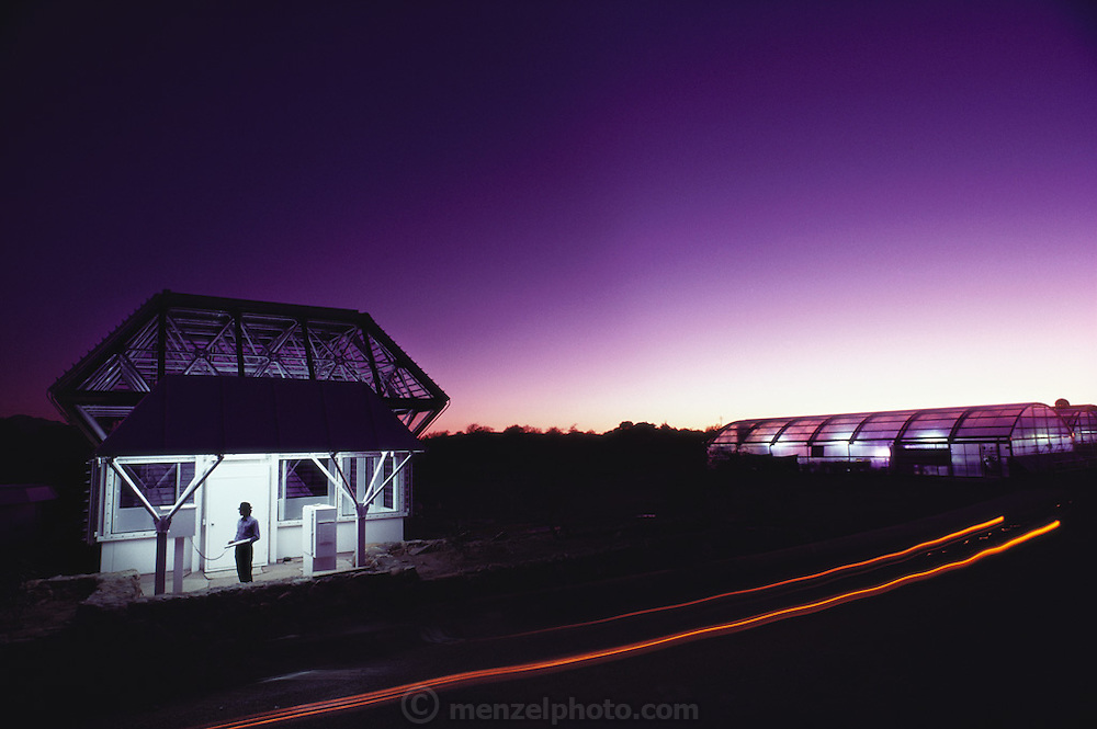 USA_SCI_BIOSPH_77_xs <br /> The Biosphere 2 Project's twenty-seven foot test module at night with auto lights passing by. Norberto Alvarez-Romo is monitoring the conditions inside while standing outside logged on to the system's computer. Biosphere 2 was a privately funded experiment, designed to investigate the way in which humans interact with a small self-sufficient ecological environment, and to look at possibilities for future planetary colonization. The $30 million Biosphere covers 2.5 acres near Tucson, Arizona, and was entirely self- contained. The eight 'Biospherian's' shared their air- and water-tight world with 3,800 species of plant and animal life. The project had problems with oxygen levels and food supply, and has been criticized over its scientific validity. 1986