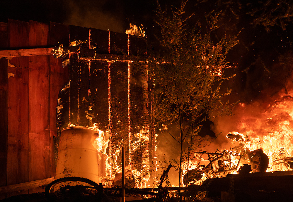 A fence at a home on Highway 236 near Boulder Creek, Calif. burns in the CZU Lightning Complex fire on Aug. 21, 2020.