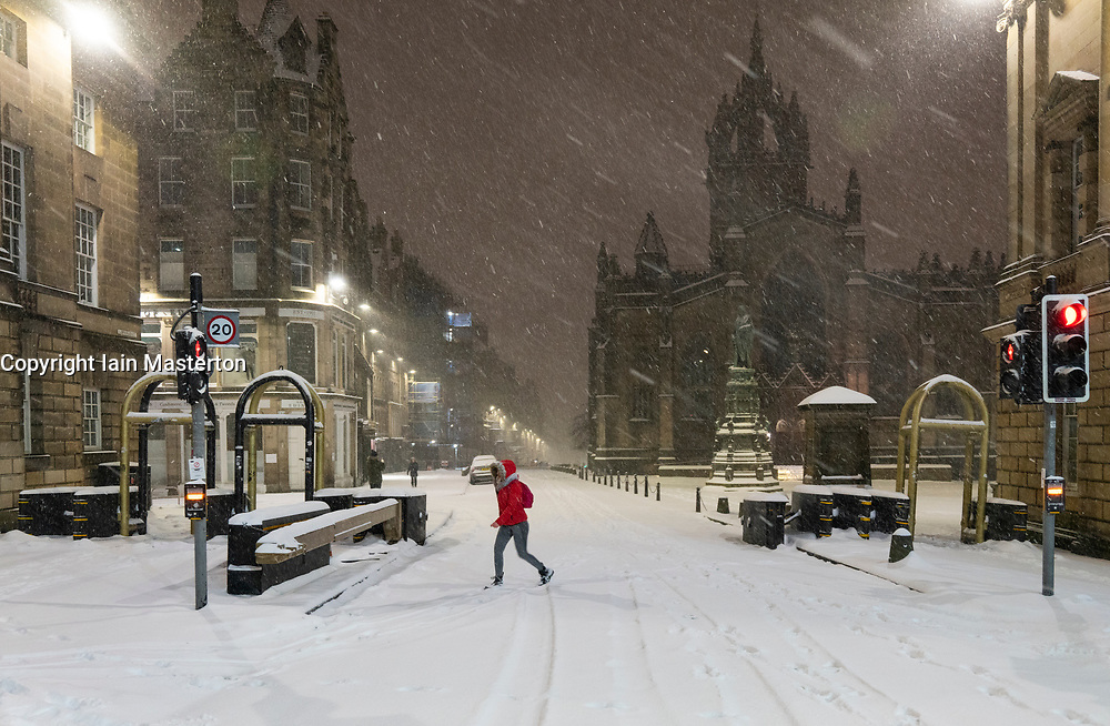 Edinburgh, Scotland, UK. 10 Feb 2021. Big freeze continues in the UK with heavy overnight and morning snow in the city. Pic; Lone member of public on the Royal Mile in the early morning snow blizzards. Iain Masterton/Alamy Live news