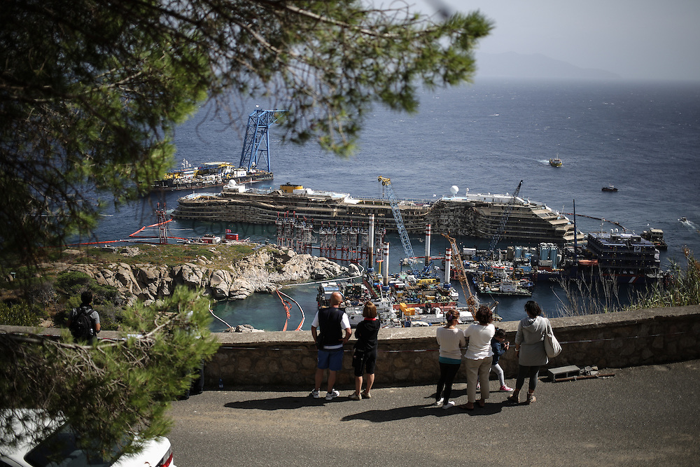Tourist and resident looking at the Costa Concordia wreck yard