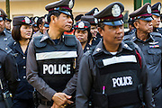 """01 FEBRUARY 2014 - BANGKOK, THAILAND: Thai police in formation to keep voters and protestors apart near the Din Daeng polling station in Bangkok. Thais went to the polls in a """"snap election"""" Sunday called in December after Prime Minister Yingluck Shinawatra dissolved the parliament in the face of large anti-government protests in Bangkok. The anti-government opposition, led by the People's Democratic Reform Committee (PDRC), called for a boycott of the election and threatened to disrupt voting. Many polling places in Bangkok were closed by protestors who blocked access to the polls or distribution of ballots. The result of the election are likely to be contested in the Thai Constitutional Court and may be invalidated because there won't be quorum in the Thai parliament.    PHOTO BY JACK KURTZ"""