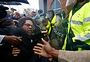 Activist Cornel West is knocked over during a scuffle with police during a protest at the Ferguson Police Department in Ferguson, Missouri, October 13, 2014. Hundreds of protesters converged in the pouring rain on the Ferguson, Missouri, police department on Monday as they launched another day of demonstrations over the August killing by police of an unarmed black teenager.    REUTERS/JIm Young