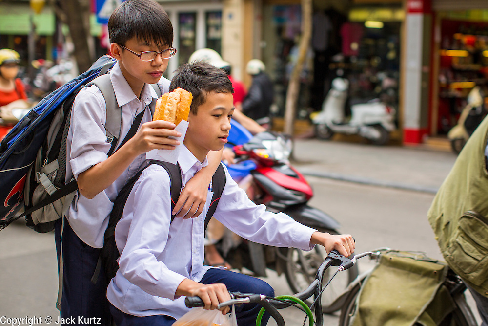 09 APRIL 2012 - HANOI, VIETNAM:  A school boy eats a baguette while he catches a ride on a friend's bike in Hanoi, the capital of Vietnam. Hanoi, established in 1010 AD, is one of the oldest permanent cities in Southeast Asia. PHOTO BY JACK KURTZ