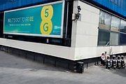 Two members of the Jehovahs Witnesses stand around the corner to a large billboard ad for phone provider EEs new 5G, the first provider to offer the new high-speed Internet and lifestyle service, on 5th June 2019, in London, England.
