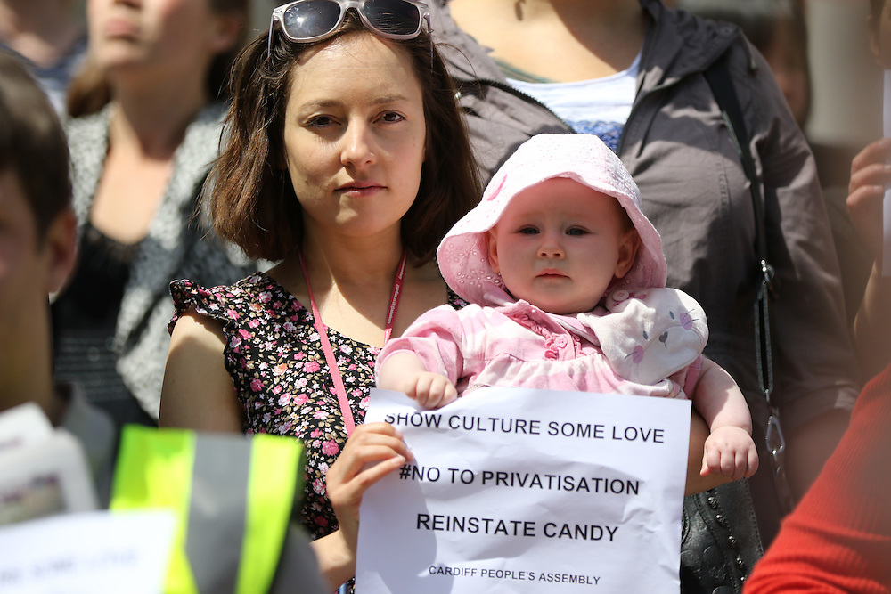 A protester and baby on the Cardiff People's Assembly anti-austerity rally displays support for the National Gallery strikers and sacked PCS (Public and Commercial Services Union) rep Candy Udwin. Outside the National Museum of Wales