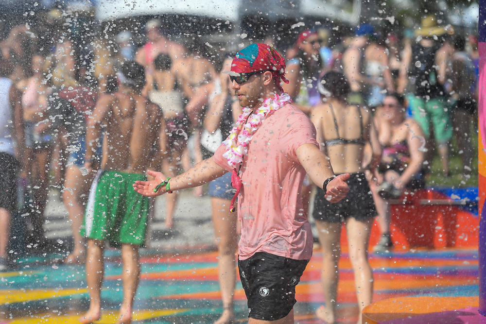 A festival goer gets relief from the heat under the huge fountain at Bonnaroo.