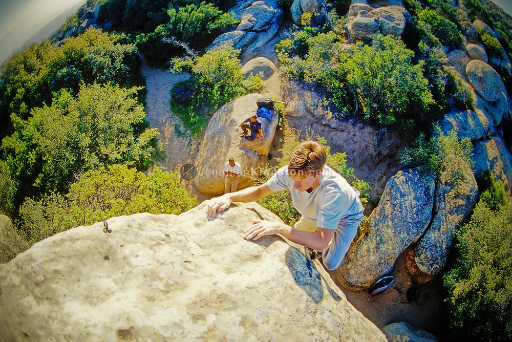 A rock climber climbs at Lizards Mouth bouldering area, Santa Barbara, California. (releasecode: jk_mr1012) (Model Released)