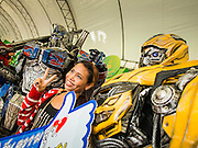 """24 JULY 2014 - BANGKOK, THAILAND:  A Thai woman poses for selfies with characters inspired by the Transformer movies at the happiness party in Bangkok. The Thai Junta is organizing a series of public events throughout Thailand meant to bolster public opinion. The events are called """"restoring happiness to the people"""" parties. They feature historic pageants, music, food, health checks and free haircuts. The party in Bangkok is on Sanam Luang, the Royal Parade Ground, which is near the Grand Palace and the Ministry of Defense.   PHOTO BY JACK KURTZ"""