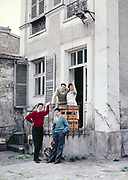 Young French woman making arm gesture with three English schoolboy students at back of cafe, France c 1960