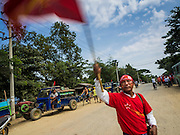 25 OCTOBER 2015 - SHWEPYITHAR, MYANMAR: A National League for Democracy (NLD) supporter waves a NLD banner while he waits for a party motorcade in Shwepyithar, Myanmar. Political parties are in fill campaign mode in Myanmar (Burma). National elections are scheduled for Sunday Nov. 8. The two principal parties are the National League for Democracy (NLD), the party of democracy icon and Nobel Peace Prize winner Aung San Suu Kyi, and the ruling Union Solidarity and Development Party (USDP), led by incumbent President Thein Sein. There are more than 30 parties campaigning for national and local offices.     PHOTO BY JACK KURTZ