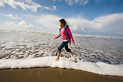 Nine year old Vira Halim-Rotinsulu runs in the surf on the beach at the Oregon Coast.