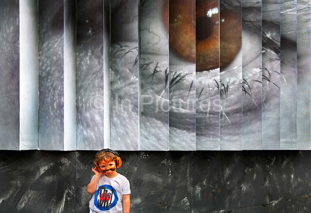 Boy with facepaint standing in front of a 3D photo of an eye by Liam Hayhow, Shangri La field, Glastonbury Festival 2016. The Glastonbury Festival is the largest greenfield festival in the world, and is now attended by around 175,000 people. Its a five-day music festival that takes place near Pilton, Somerset, United Kingdom. In addition to contemporary music, the festival hosts dance, comedy, theatre, circus, cabaret, and other arts. Held at Worthy Farm in Pilton, leading pop and rock artists have headlined, alongside thousands of others appearing on smaller stages and performance areas.