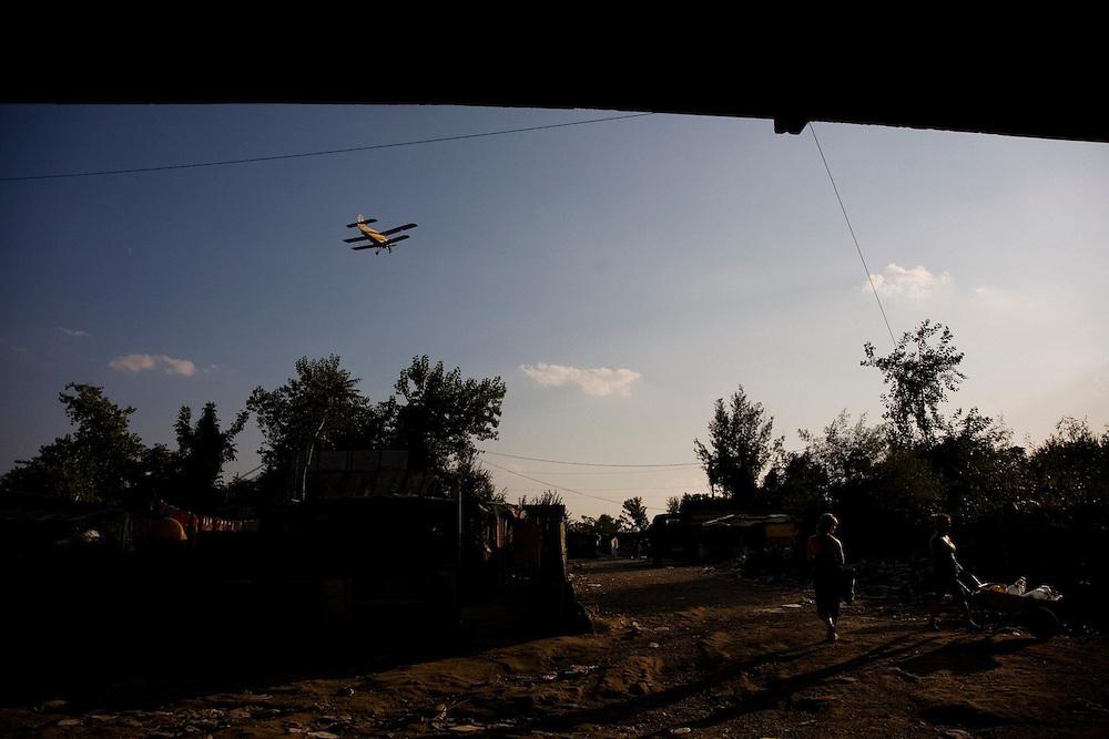 An airplane spraying pesticides to kills mosquitos along the Sava river flies over the Nova Gazela camp.