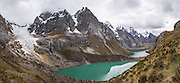 A glacier from Siula Grande and Nevado Sarapo feeds Lake Quesillococha (4332 m) and Lake Siula in the Cordillera Huayhuash, Andes Mountains, Peru, South America. This photo is at viewpoint halfway up the pass of Siula Punta, on Day 3 of 9 days trekking around the Cordillera Huayhuash. This panorama was stitched from 7 overlapping photos.