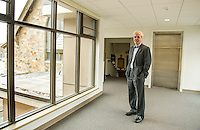 "Reverend Dr. Warren Bouton stands in the newly finished ""bridge"" connecting the Congregational Church directly with the office complex on one level.  (Karen Bobotas/for the Laconia Daily Sun)"