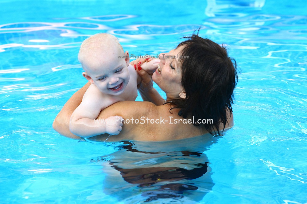 Grandmother with grandson in a swimming pool Model release available