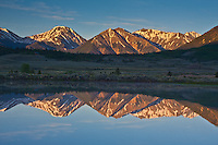 Reflections of Twin Peaks, (center) Mount Hope (left) Rinker Peak (right) of the Sawatch Range in a small reservoir in the Upper Arkansas Valley.  Colorado, USA.