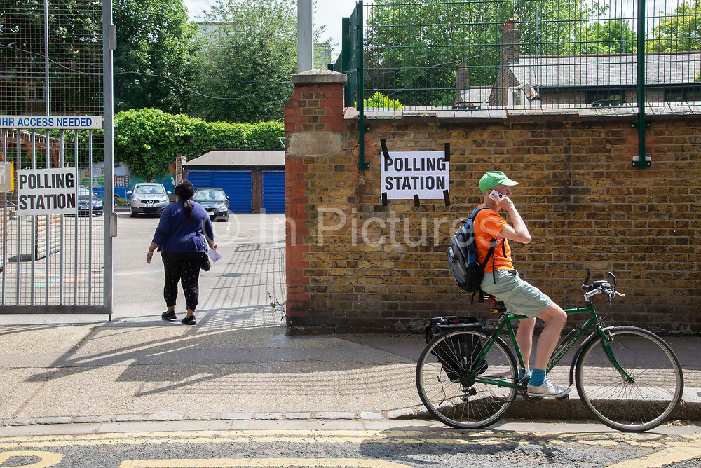 A man speaks on his mobile phone as a women arrives to cast her vote at a polling station on 23rd May 2019 in Greenwich ,South- East London, England, United Kingdom. Polls are open for the European Parliament elections. Voters will choose 73 MEPs in 12 multi-member regional constituencies in the UK with results announced once all EU nations have voted. The voting process is expected to be completed by 10pm on Sunday.