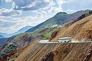 Tour buses negotiate the colorful Polychrome Pass near mile 46 on the Denali Park Road, Alaska.
