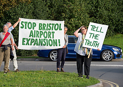 © Licensed to London News Pictures. 29/08/2019. Felton, North Somerset, UK. Extinction Rebellion protest outside Bristol Airport against the proposed expansion plans for Bristol Airport, with one protestor climbing and hanging a banner off the sculpture on the roundabout in front of the airport entrance. The campaigners say that there will be more air pollution from increased flights which are not counted in the airport's target to be carbon neutral by 2025, that there will be a loss of greenbelt land, more noise pollution from more flying, traffic congestion, and ill health from respiratory and cardiac disease. Campaigners say a recent report found that the incidence of asthma and respiratory diseases was on average 17% higher among those living within 6.2 miles of a major airport and that cardiac diseases were 9% more common. Photo credit: Simon Chapman/LNP.