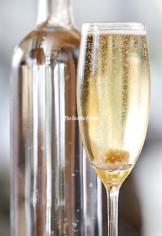 A Prosecco cocktail, served with a fizzing raw sugar cube and grapefruit bitters. (Sy Bean / The Seattle Times)