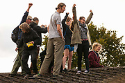 Housing activists cheer as they occupy a rooftop on the Sweets Way housing estate close to the home of its last surviving resident, Mostafa Aliverdipour, on 23rd September 2015 in London, United Kingdom. A group of housing activists calling for better social housing provision in London had occupied some of the properties on the 142-home estate in Whetstone, in some cases refurbishing properties intentionally destroyed by the legal owners following eviction of the original residents, in order to try to prevent or delay the eviction of Mr Aliverdipour and the planned demolition and redevelopment of the entire estate by Barnet Council and Annington Property Ltd.