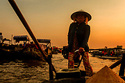 Tour boat operator taking us to Cal Rang Floating Market in Can Tho at sunrise.