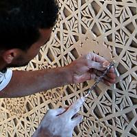 Africa, Morocco, Marrakesh. Craftsman sculpting Islamic patterns.