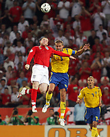 Photo: Chris Ratcliffe.<br /> Sweden v England. FIFA World Cup 2006. 20/06/2006.<br /> Olof Melberg of Sweden clashes with Wayne Rooney of England.