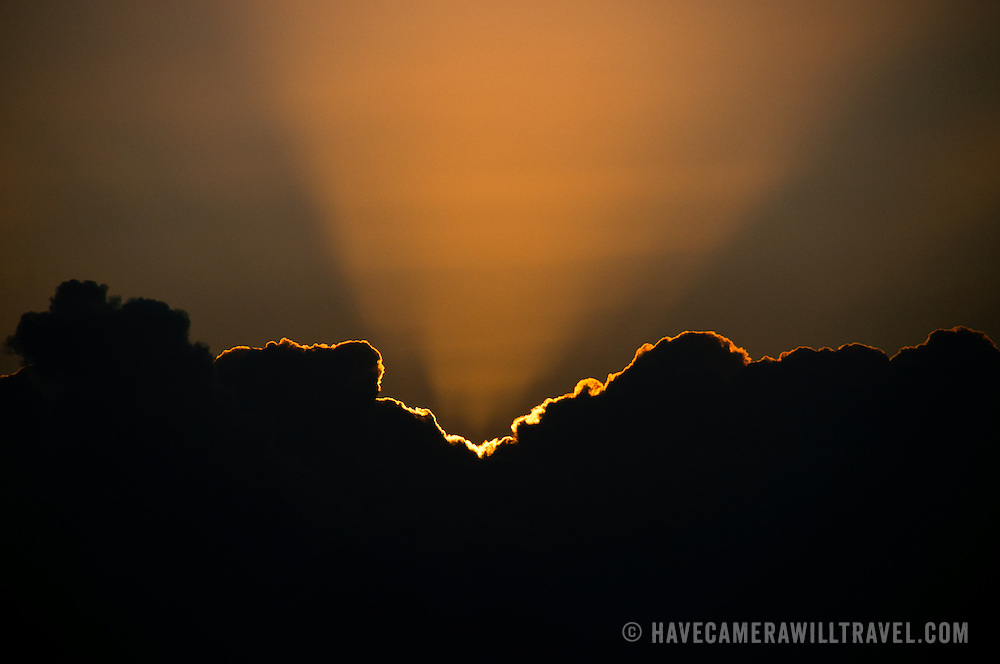 The golden rays of the setting sun create a golden lining to the edge of a cloud. Photo was taken at sunset on Swains Reef on Queensland's Great Barrier Reef, Australia.