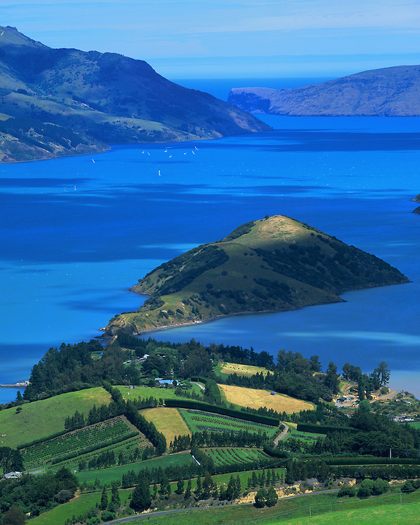 Akaroa Harbour reflects brilliant blue with lush green countryside surrounding New Zealand first French colony.