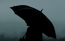 A racegoer in the rain during day one of the November Meeting at Cheltenham Racecourse, Cheltenham
