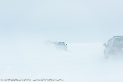 A convoy of vehicles drives 30-miles across Lake Baikal on the meter-thick ice after the Baikal Mile Ice Speed Festival. Maksimiha, Siberia, Russia. Sunday, March 1, 2020. Photography ©2020 Michael Lichter.
