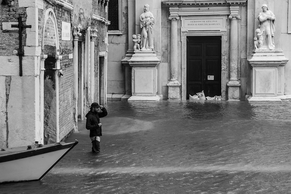 Venice, Italy. 29 October, 2018. A boy walk in a flooded small square in Cannaregio district on October 29, 2018, in Venice, Italy. This is a selection of pictures of different areas of Venice that the press has not covered, were resident live and every year they have to struggle with the high tide. Due to the exceptional level of the 'acqua alta' or 'High Tide' that reached 156 cm today, Venetian schools and hospitals were closed by the authorities, and citizens were advised against leaving their homes. This level of High Tide has been reached in 1979. © Simone Padovani / Awakening / Alamy Live News