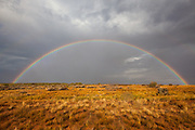 A complete arch of a rainbow in a field outside of Moab, Utah