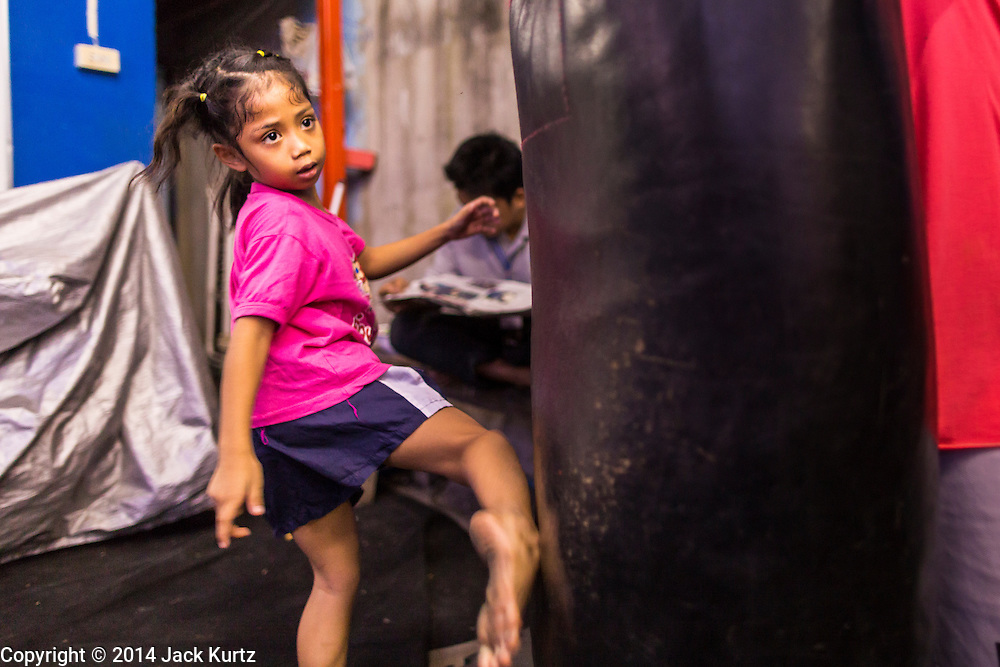 """18 DECEMBER 2104 - BANGKOK, THAILAND: A girl who wants to box works out by kicking a heavy bag at the Kanisorn gym. The Kanisorn boxing gym is a small gym along the Wong Wian Yai - Samut Sakhon train tracks. Young people from the nearby communities come to the gym to learn Thai boxing. Muay Thai (Muai Thai) is a Thai fighting sport that uses stand-up striking along with various clinching techniques. It is sometimes known as """"the art of eight limbs"""" because it is characterized by the combined use of fists, elbows, knees, shins, being associated with a good physical preparation that makes a full-contact fighter very efficient. Muay Thai became widespread internationally in the twentieth century, when practitioners defeated notable practitioners of other martial arts. A professional league is governed by the World Muay Thai Council. Muay Thai is frequently seen as a way out of poverty for young Thais and Muay Thai camps and schools are frequently crowded. Muay Thai professionals and champions are often celebrities in Thailand.     PHOTO BY JACK KURTZ"""