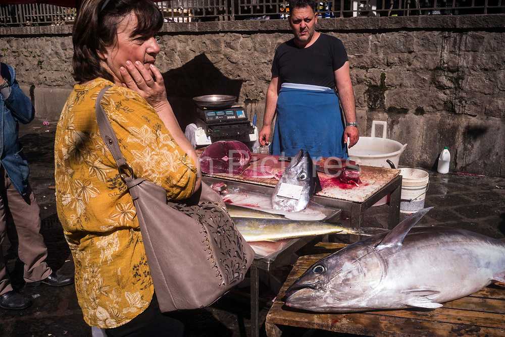 Stallholders selling tuna to a female customer at the Mercato della Pescheria Market wait for customers. Catania, Sicily, Italy. A fish market has been held every day in Piazza Alonzo di Benedetto since the beginning of the 19th century, although there has likely been a market here for centuries. and is the most important market in Catania.