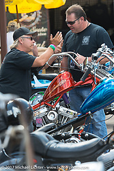 Eric Greenfield speaks with Roadside Marty about his '88 evo chopper at The Cycle Source bike show at the Broken Spoke at the Iron Horse Saloon during the annual Sturgis Black Hills Motorcycle Rally.  SD, USA. Thursday August 10, 2017.  Photography ©2017 Michael Lichter.