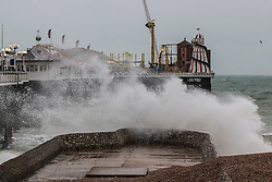 © Licensed to London News Pictures. 14/11/2015. Brighton, UK. Brighton beach is battered by strong winds and powerful waves as people shelter under their umbrella. Today November 14th 2015. Photo credit : Hugo Michiels/LNP