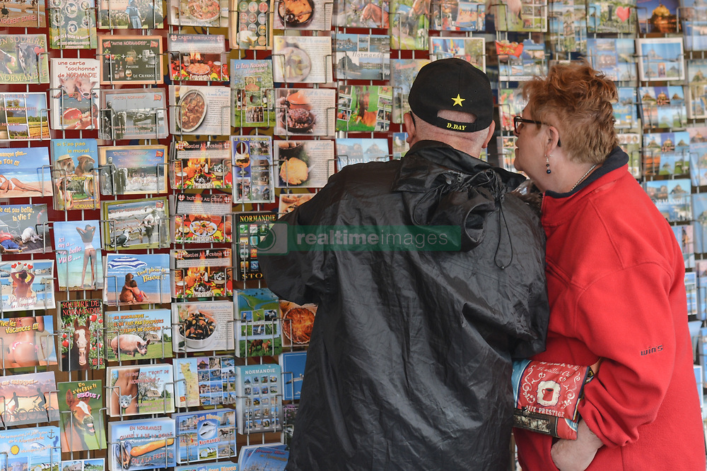 June 6, 2017 - Sainte-Mere-Eglise, France - A couple of tourists outside a shop with post-cards and souvenirs in Sainte-Mere-Eglise..Tuesday 6th June is the 73rd anniversary of the D-Day landings which saw 156,000 troops from the allied countries including the United Kingdom and the United States join forces to launch an audacious attack on the beaches of Normandy..On Tuesday, June 6, 2017, in Sainte-Mere-Eglise, Manche, France. (Credit Image: © Artur Widak/NurPhoto via ZUMA Press)
