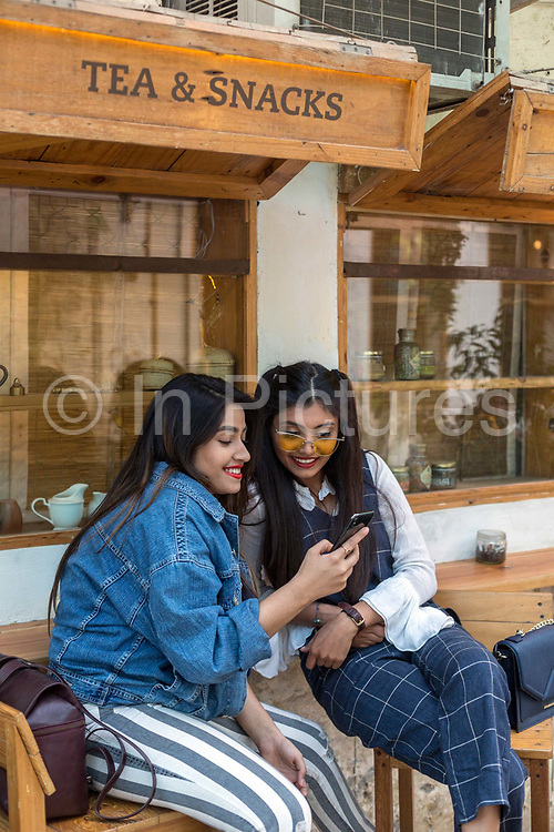Two young women pose for selfies outside a coffee shop in Champa Gali, New Delhi, India. Champa Gali is the latest and most intimate of Delhis urban creative villages.